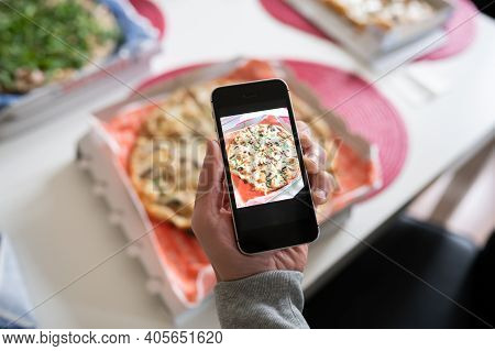 Blogger Taking Photo Of Tasty Pizza With Smart Phone, Closeup. Copy Space
