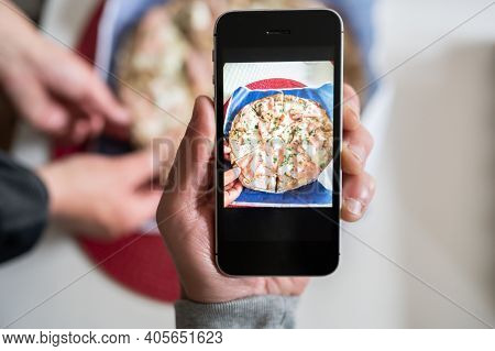 Young Man An Taking Photo With Smart Phone Of A Pizza During A Friends Meal.copy Space