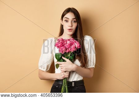 Valentines Day. Image Of Surprised Girlfriend Thanking For Flowers, Receive Pink Roses From Lover An