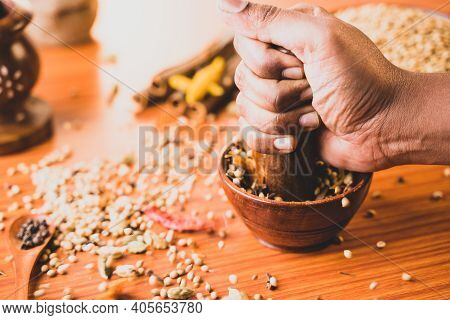 Close Up Of Hands Hitting Or Smashing Indian Mixed Masala Spices In The Wooden Bowl Or Spice Grinder
