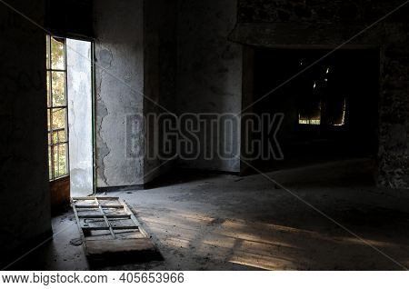 Empty Abandoned Room With Broken Door And Dramatic Bright Sunlight Entering The Place