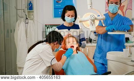 Woman Orthodontist Lighting The Lamp Examining Little Patient Using Sterile Dental Tools In Stomatol