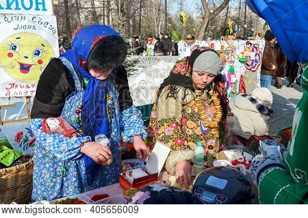 Chelyabinsk, Russia, March 2, 2014. Russian national holiday of farewell to winter. Slavic holiday Maslenitsa. Women in national costumes of the people are treated to tea and bagels.
