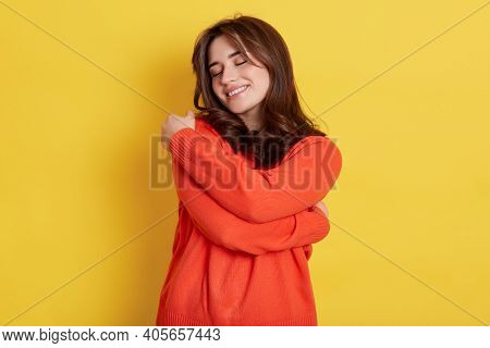 Lovely Happy European Woman Daydreams, Embraces Herself With Both Hands, Recalls Romantic Event, Fee