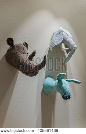 Felted Animals Toys Hanging On The Wall. Heads Of Donkey, Rhinoceros And Elephant On Gray Wall. Emul