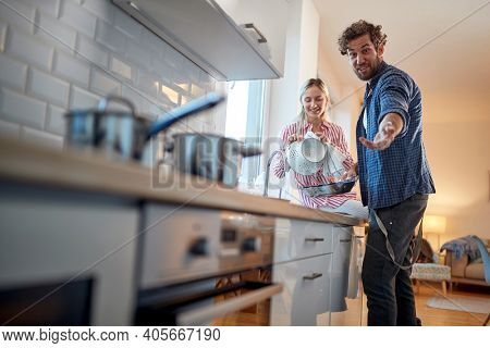 Happy couple posing for a photo and doing housework in a cheerful atmosphere in the kitchen. Kitchen, housework, home, relationship