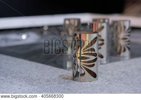 Cylindrical Metal Workpieces With Holes Of Different Sizes And Forms After Laser Cutting Process At