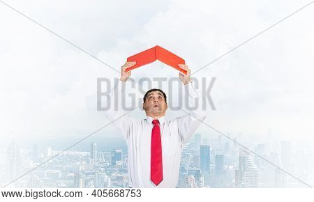 Senior Businessman Holding Open Diary Overhead As Roof. Man In White Shirt And Tie Standing On Cloud
