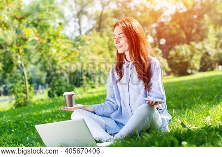 Young Redhead Woman Meditating In Lotus Pose With Laptop And Cup Of Coffee On Green Grass. Beautiful