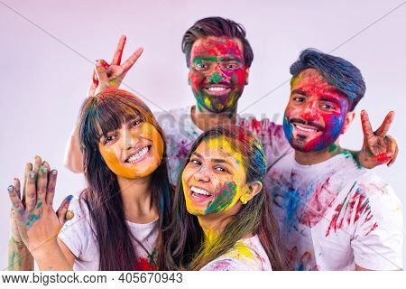 Four Indian Students Painted In Colors Celebrating Holi Festival In Studio White Isolate Background