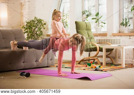 Plank With Daughter On Back. Young Woman Exercising Fitness, Aerobic, Yoga At Home, Sporty Lifestyle