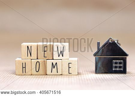 New Home Text Written With Wooden Cubes Background With Symbol Of Cozy Little House With Blurred Bac