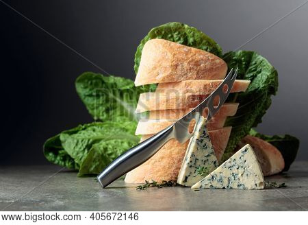 Blue Cheese Slices With Bread, Lettuce, Thyme, And Cheese Knife.