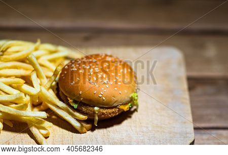 French Fries And Chicken Burger On A Wooden Table. Food, Junk Food And Fast Food Concept