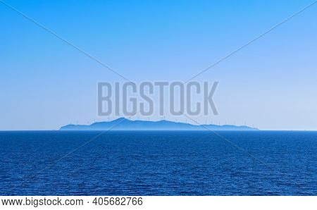 Seascape Of Calm Azure Sea, Blue Sky, No Clouds. Distant Island In Haze With Silhouettes Of Electric