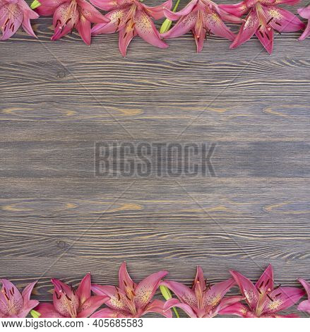 Frame Of Beautiful Pink Lilies On A Brown Wooden Background With Copy Space For Text