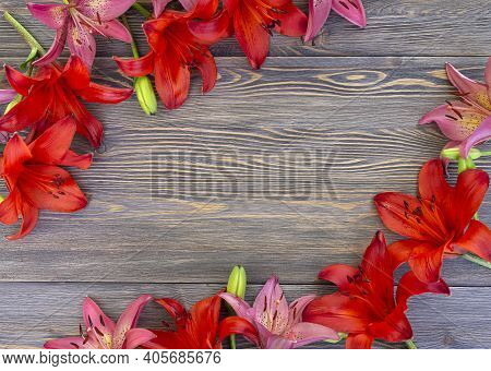 Frame Of Beautiful Pink And Red Flowers Of Lilies On Brown Wooden Background With Copy Space For Tex