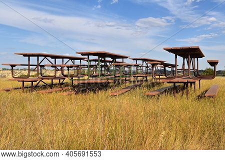 Picnic Tables Are Stacked In Rows On The Prairie Grass With The Badlands In The Horizon