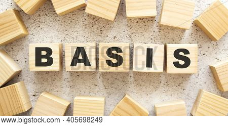 The Word Basis Consists Of Wooden Cubes With Letters, Top View On A Light Background. Work Space.