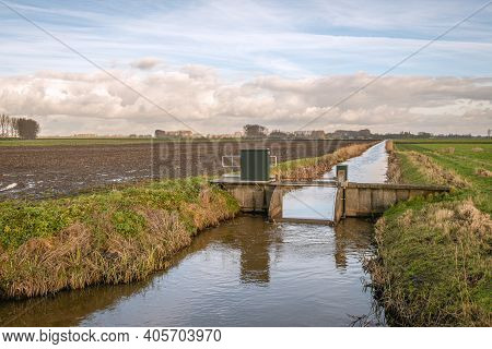 Small Weir In A Ditch In A Dutch Polder. The Weir Is Operated From A Distance By The Water Board. Th
