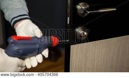 Drilling A Door Lock, Repairing Interior Doors, A Man Fixes The Core Of The Door Lock.