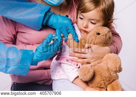 The Girl Looks At The Syringe With Fear. The Doctors Hands Are Injected Into The Forearm. Vaccinatio
