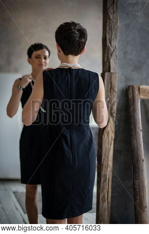Young Attractive Brunette Woman In Black Dress Reflects In The Mirror With Her Back To The Camera An