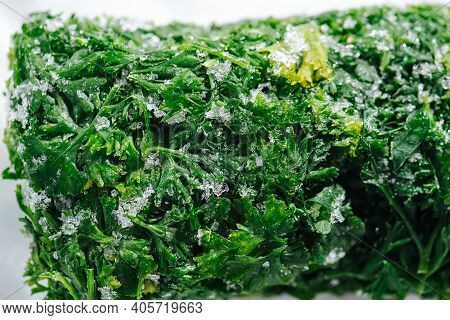 Close Up Image Of Frozen Parsley Green Briquette Covered With Tiny Ice Crystals.