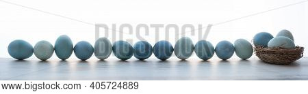 Blue Pastel Dyed Easter Eggs In A Row On Gray Surface. Horizontal Background For Easter Greetings Wi