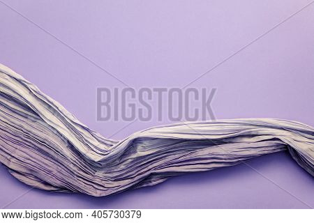Top View Of Crinkled Fabric On Purple Background. Fine Lustrous Silk Or Synthetic Fabric With Crisp