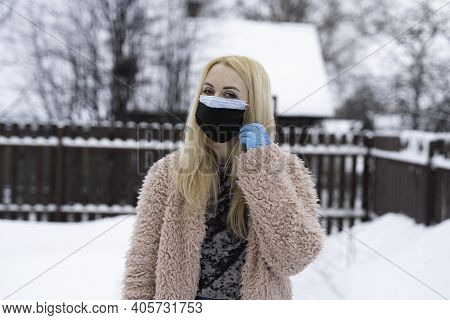 Double Mask On The Face. A Girl In Half A Turn, With Two Masks On Her Face And A Blue Medical Glove