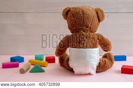 Baby Girl, Teddy Wearing Diaper Playing With Colorful Wooden Blocks On Pink Color Floor