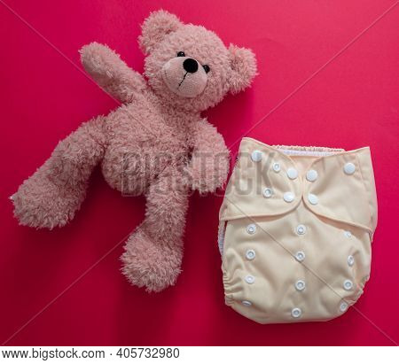 Reusable Cloth Baby Diaper. Eco Friendly Nappy And Teddy Bear On Red Background.