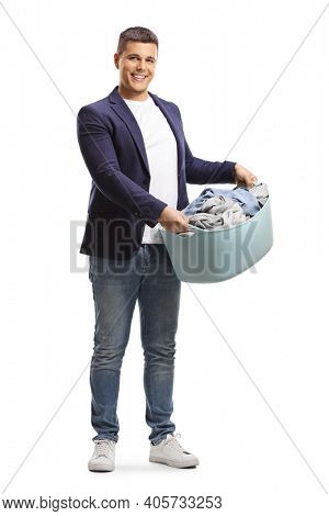 Full length portrait of a young man holding a full laundry basket isolated on white background