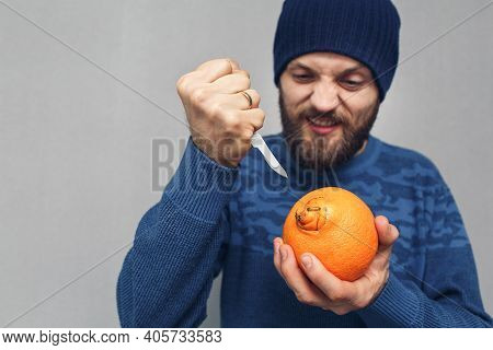 An Angry Bearded Man Wants To Cut Out The Navel Of An Orange With A Scalpel. Concept Of Problems Due