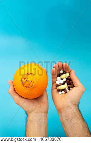Orange With A Large Navel, Pills In Hands On A Blue Background. Hemorrhoid Drug Treatment Concept.