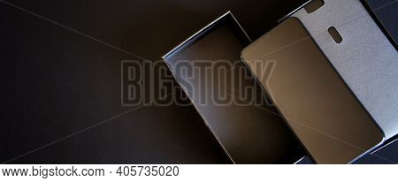 Unboxing Of A Large Modern Black Smartphone Out Of The Box On A Dark Background. View From Above. Fr