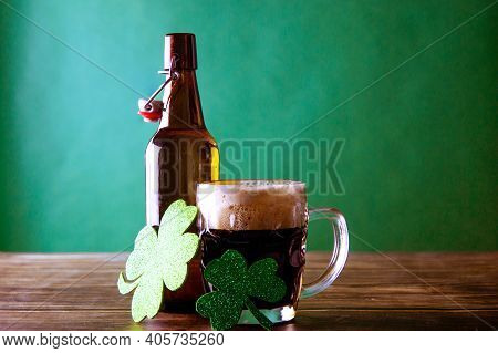 A Mug Of Dark Beer With Its Open Bottle On A Green Background And A Wooden Table, Next To Them Two S