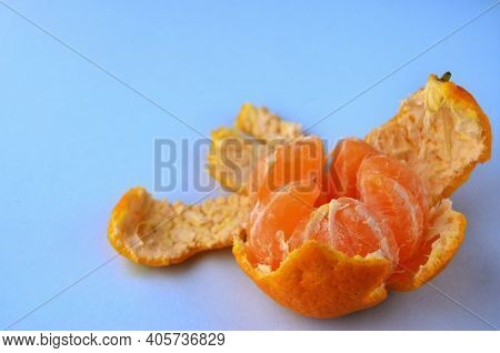 One Fresh Peeled Tangerine In An Open Peel On A Blue Table With A Copy Space