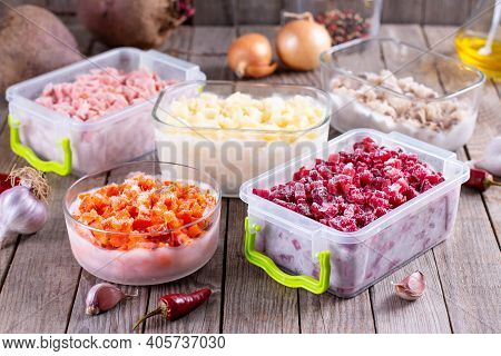 Assortment Of Frozen Vegetables In Containers On A Wooden Table. Frozen Food