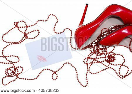 Beautiful Female Shiny Red Stilettos And A Card With A Lipstick Print  On A White Background