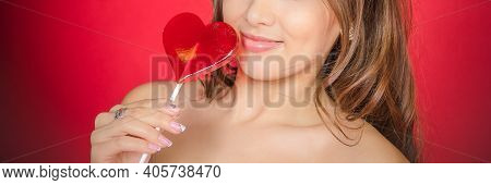 Woman Bites Off Red Lollipop In The Shape Of Heart.beautiful Sexy Woman Model With Pink Lips And Lol