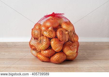 5 Kg Farm Onions In A Red Pp Mesh Bag. Polypropylene Net Sack With 11 Lb Of Organic Onions On A Brow