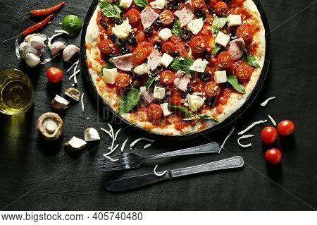 Portrait Of Pizza With Cheese And Olive Seed And Brown Wooden Background. Pizza Is A Savory Dish Of