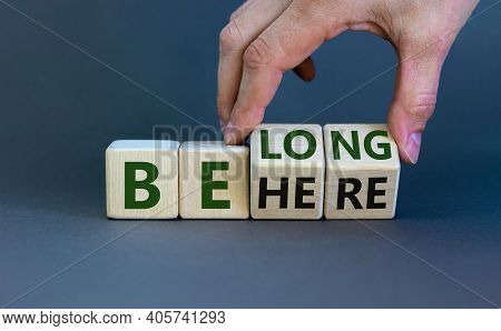 Be Here Belong Symbol. Businessman Hand Turns Cubes And Changes Words 'be Here' To 'belong'. Beautif