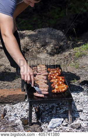 Man Turning Delicious Grilled Meat By Fork Preparing Bbq For Friends And Family. Bosnian Cevapi And