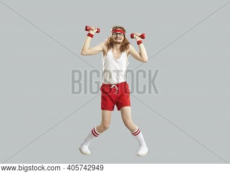 Funny Tired Skinny Man Doing Exercise With Gym Dumbbells Isolated On Gray Background