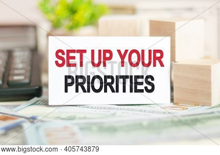The Word Set Up Your Priorities Is Written On White Paper Card Near A Wooden Cubes, Calculator On A
