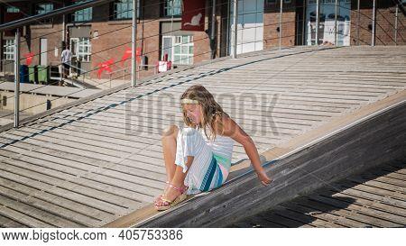 Beautiful Little Girl Having Fun, Sliding Down On A Median Strip Of Wooden Wavy Bridge In Downtown T