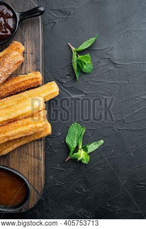 Churros With Caramel, Traditional Spanish Cusine, On Black Background, Top View Flat Lay With Space